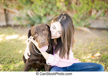 Attractive woman and dog cuddle