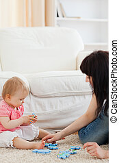 Attractive woman and her baby playing with puzzle pieces while sitting on a carpet in the living room