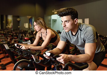 Couple in a spinning class wearing sportswear. - Attractive ...