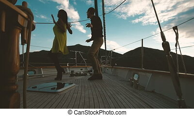Attractive woman and man dancing on deck of ship in evening.