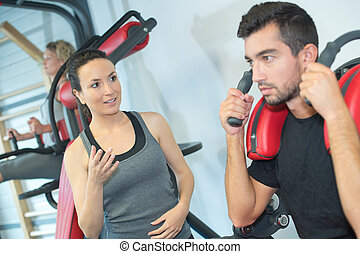 attractive woman and man exercising at gym