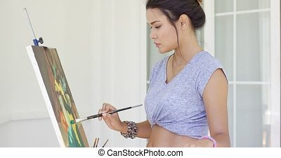 Attractive woman artist painting on her patio standing...