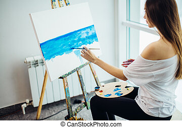 Attractive woman artist painting sea-scape in workshop - ...