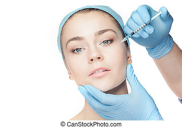 Attractive woman at plastic surgery with syringe in her face...