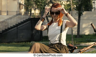 Attractive woman bicyclist in sunglasses enjoying a sunny...