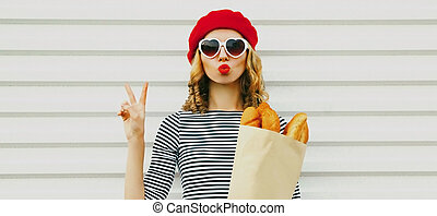 Attractive woman blowing red lips sending sweet air kiss, grocery shopping paper bag with long white bread baguette wearing a french red beret over white background
