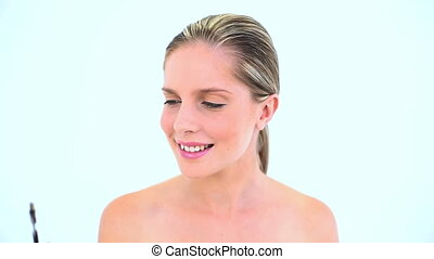 Attractive woman brushing her eyebrows