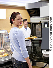 Attractive woman buying baguette in a cafeteria with baker in the background both looking at the camera
