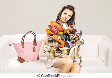 Attractive woman carrying a heap of shoes - Attractive lady...