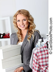 Attractive woman carrying shoe boxes in store