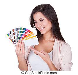 Attractive woman chooses a color scheme. Studio portrait...