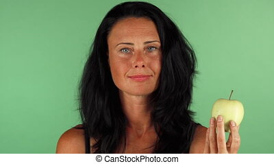 Attractive woman choosing between chocolate and an apple -...