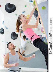 attractive woman climbing up the wall in gym
