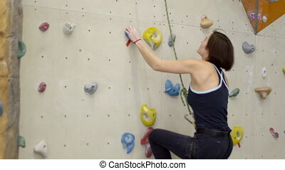 Attractive woman climbs actively on climbing wall indoors....