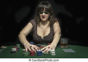 Attractive woman collects his winnings in a game of poker