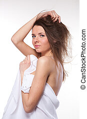 Attractive woman covered in white cloth on white
