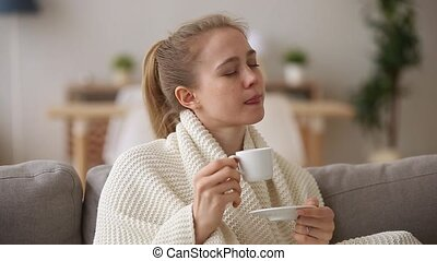 Attractive woman covered with plaid drinking morning coffee...