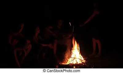 Attractive woman dancing by the campfire and her friends singing and clapping at night
