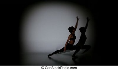 Attractive woman dancing contemporary dance on black background, spot light