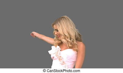 Attractive woman dancing in wedding gown on grey screen in...