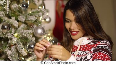 Attractive woman decorating a Christmas tree attaching...