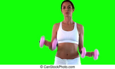 Attractive woman doing exercise with dumbells over a green...