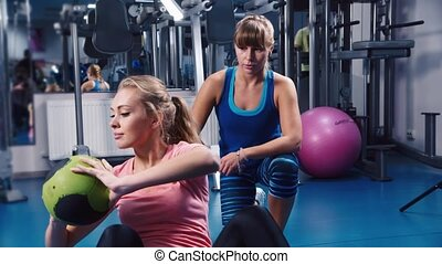 Attractive woman doing exercises for the press under the supervision of a coach