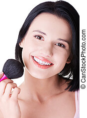 Attractive woman doing make-up on face.