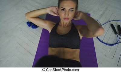 Attractive woman doing press exercise on a lilac mat in gym, close-up