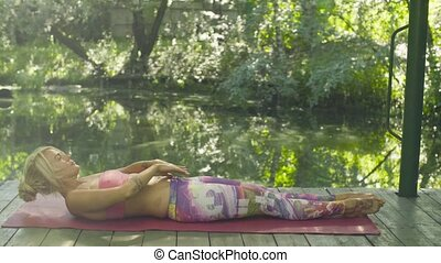 Attractive woman doing yoga exercises outdoors