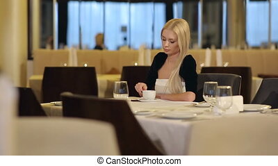 Attractive Woman Drinking Coffee at Restaurant
