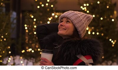 Attractive woman drinking coffee using a mobile phone while walking through the streets on the background of the festive lights of the night city. Glowing blurred bokeh lights of Christmas