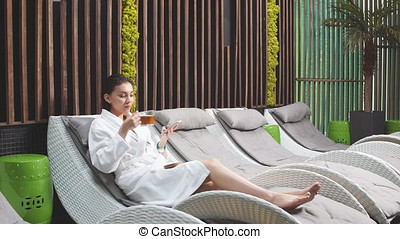 Attractive Woman Drinking Tea and Using Smart Phone in Spa...