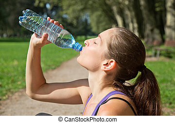 Attractive woman drinking water after sports