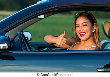 Attractive woman driver doing thumbs up in car.