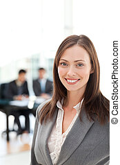 Attractive woman during a meeting with two businessmen sitting in the bakcground