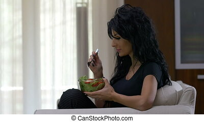 Attractive woman eating a bowl of lettuce and tomatoes vegetable salad dish watching tv at home