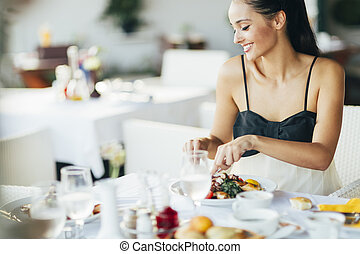 Attractive woman eating in restaurant