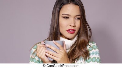Attractive woman enjoying a hot beverage - Attractive young...
