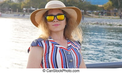 Attractive woman enjoying summer day by the sea.