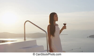 Attractive woman with glass of red wine walking down steps of swimming pool. Female is at resort by sea during sunset. She is in her white sundress during vacation.