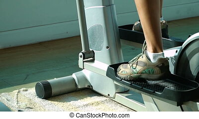 Attractive woman exercising on a stair stepper.