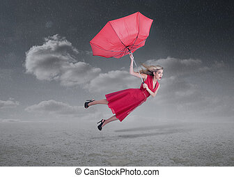 Attractive woman flying with a broken umbrella during a...