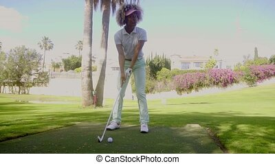Attractive woman golfer playing a shot lining up her ball...