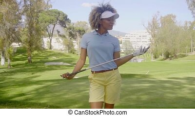 Attractive woman golfer walking on the course - Attractive...