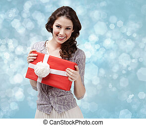 Attractive woman hands a present with white bow