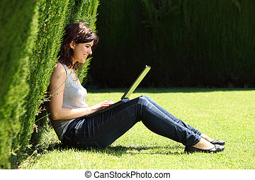 Attractive woman happy in a park with a laptop