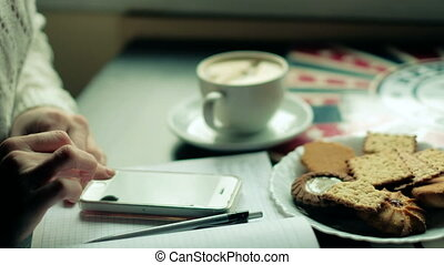attractive woman has a cup of tea in restaurant and making...