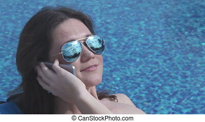 """Attractive woman having phone call, sun reflection in sunglasses"""