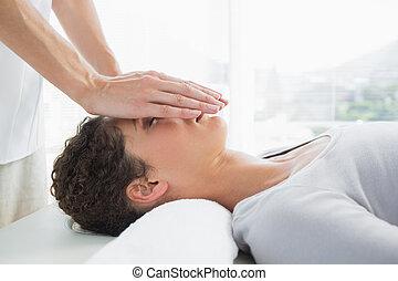 Attractive woman having reiki treatment